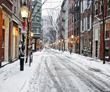 beautiful image of snow covered street with christmas lights on a snowy afternoon in bostons beacon hill